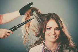 picture of tong  - Hairdresser curling woman hair with electric iron curler tong - JPG
