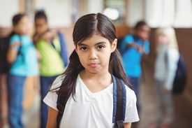 picture of school bullying  - Portrait of sad pupil being bullied by classmates at corridor in school - JPG