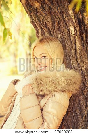 Beautiful elegant smiling blonde woman posing in autumn  park standing near the tree dressed in beige jacket with fur hoodie.
