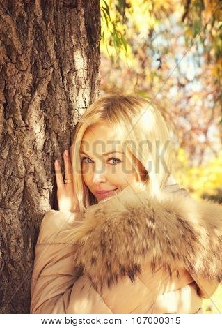 Young smiling blonde woman portrait, posing in autumn  park, dressed in beige jacket with fur hoodie.