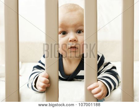 Baby lying in bed and look across wooden sticks