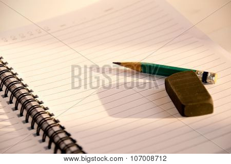 Green Pencil and black eraser placed on a notebook and sunlight