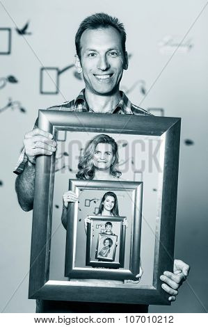 Happy father holding portrait with his family