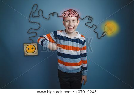 Boy shows his index finger down and laughs charging cord plug wi