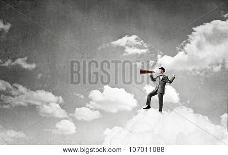 Young businessman on cloud screaming emotionally in paper trumpet