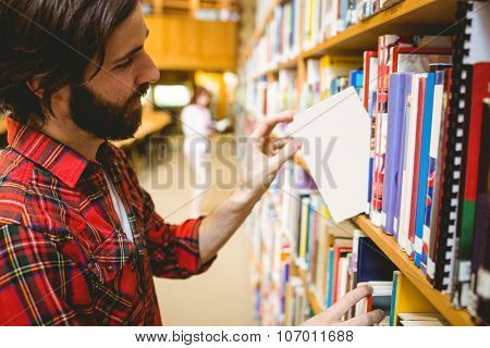 Hipster student picking a book in library at the university