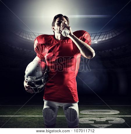 Thirsty sportsman in red jersey holding helmet while drinking water against american football arena