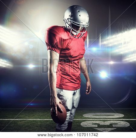 American football player with ball looking down against american football arena
