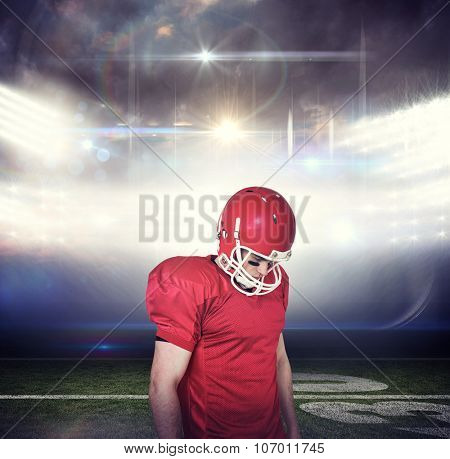 Unsmiling american football player looking down against american football arena