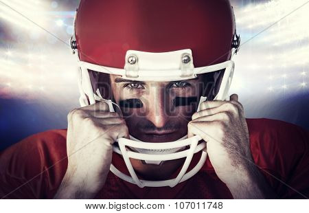 Portrait of rugby player wit hands on helmet against american football arena