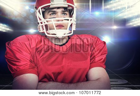 American football player with arms crossed against american football arena