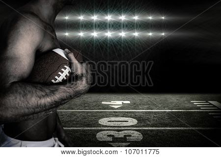 Side view of shirtless rugby player holding ball against spotlights