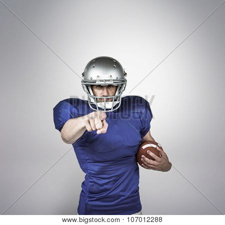 Portrait sports player pointing against grey background