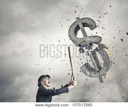 Young pretty woman in suit and hat crashing dollar sign with baseball bat