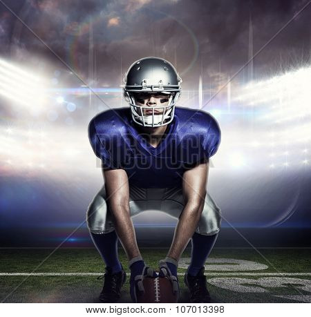 American football player with ball crouching against american football arena