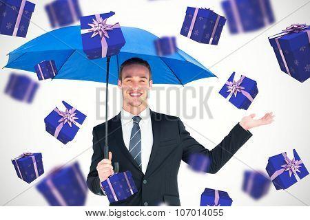 Businessman sheltering under black umbrella against purple presents