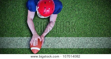 American football player scoring a touchdown against pitch with line