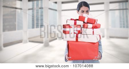 Fired businesswoman holding box of belongings against modern room overlooking city