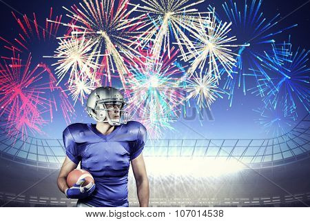 Confident American football player looking away against fireworks exploding over football stadium