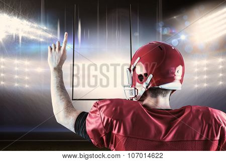 Rear view of american football player triumphing against american football arena