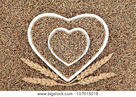 Rye grain in heart shaped bowls with wheat sheaths forming an abstract background.