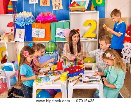 Group kids holding colored paper and glue on table in kindergarten .