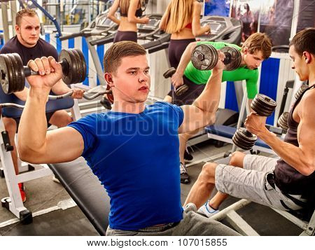 Group people and man in blue clothing working his arms and back at gym. He lying on bench and lifting barbell.