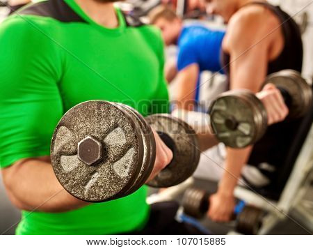 Close up of man working his arms with dumbbells at gym. He lifting dumbbells.