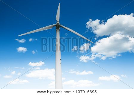 Wind Energy Turbine And Fluffy Clouds In The Sky
