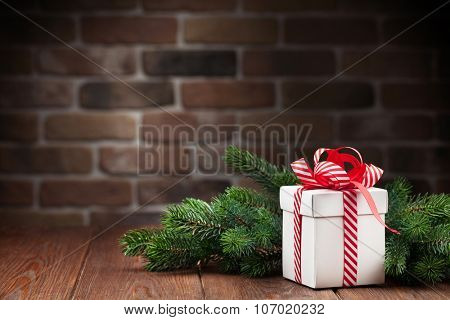 Christmas gift box and fir tree branch on wooden table. View with copy space