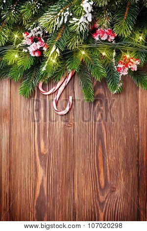 Fir tree branch with christmas lights and candy canes on wooden background with copy space