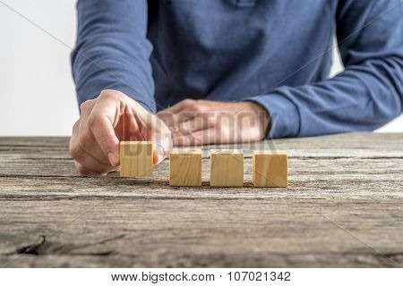 Male Hand Placing Four Blank Wooden Cubes In A Row