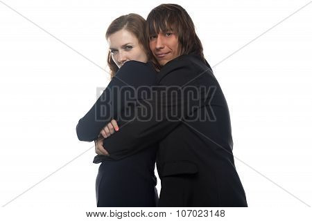 Woman and smiling man in black jacket holding her