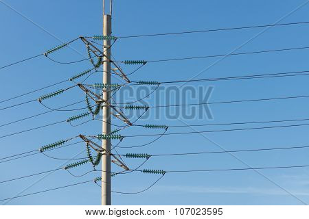 High Voltage Power Pole Against The Blue Sky