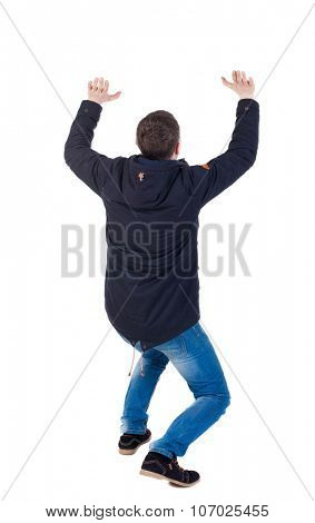 back view. man  in parka protects hands from what is falling from above. Man holding a heavy load Rear view people collection.  backside view of person.  Isolated over white background.
