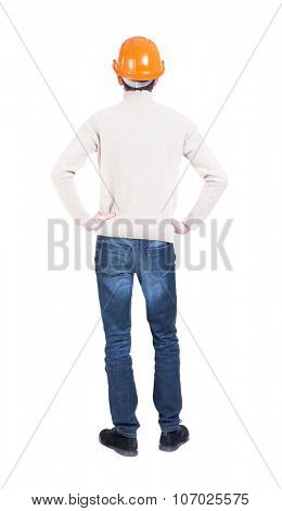 Backview of an engineer in construction helmet stands. Standing young guy. Rear view people collection.  backside view of person. Isolated over white background. Engineer hands on hips looking forward