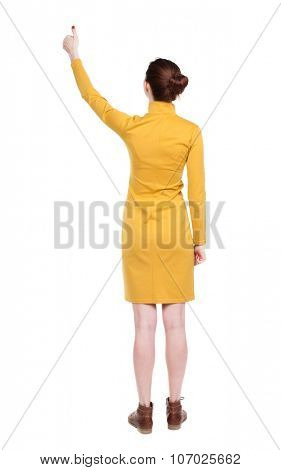 Back view of  woman thumbs up. Rear view people collection. backside view of person. Isolated over white background. Girl in mustard strict dress shows thumb of his right hand.