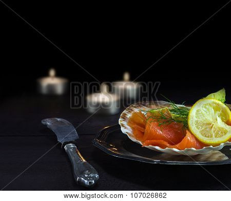 Salmon With Avocado In A Scallop Shell On A Silver Plate And Candles On Dark Wood