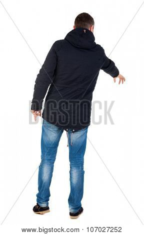 Back view of  pointing young men in parka. Young guy  gesture. Rear view people collection. backside view of person.  Isolated over white background. Man in warm jacket with his left hand points down