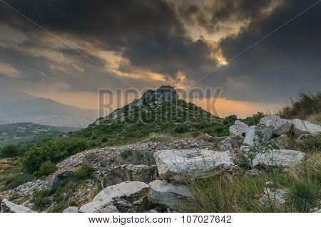 Pendeli's mountain in Greece with a rock at the top against a dramatic sky in autumn season.