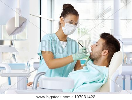 Young man on dental check-up, examined by female dentist.