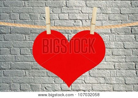 Red Heart Hang On Clothespins Over Brick Background
