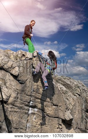 . Female climbers helping each other on rock wall
