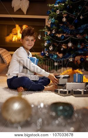 Happy schoolboy with christmas presents, sitting on floor, looking at camera.