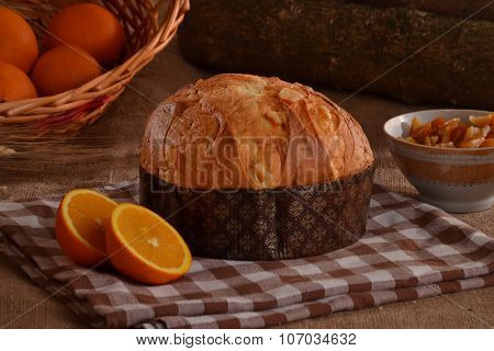 Orange panettone bread and ingredients on rustic wood ambient.Panetone and ingredients.Traditional italian christmas food.