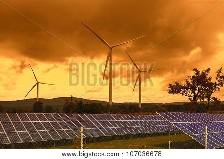 Wind turbines with solar panels in the sunset