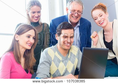University college students with professor in seminar using laptop for project team work