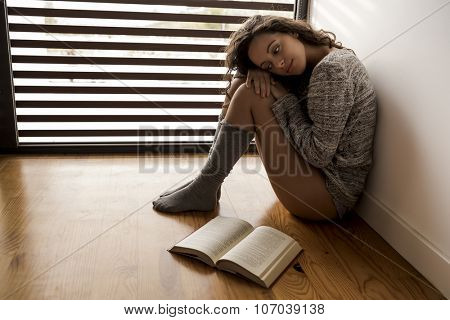 Woman sitting on the floor after reading a book