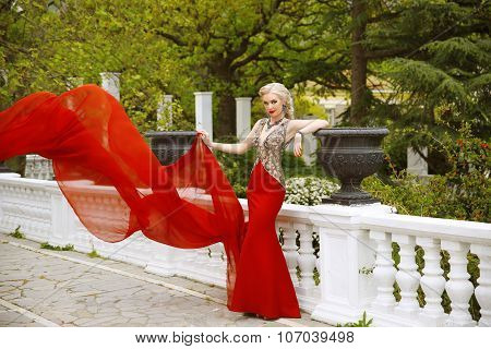 Fashion Outdoor Photo Of Beautiful Sexy Woman In Gorgeous Mermaid Red Dress With Waving Flying Fabri