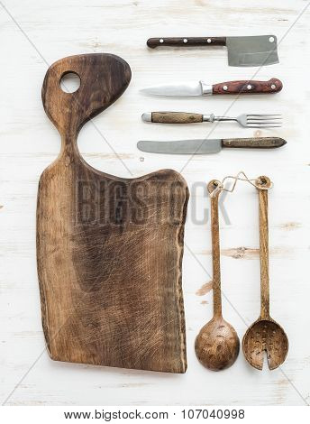 Kitchen-ware set. Old rustic chopping board made of walnut wood, knives, fork and salad spoons on a